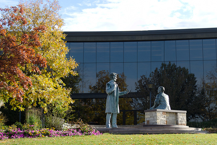 outside view of business building with statues and trees