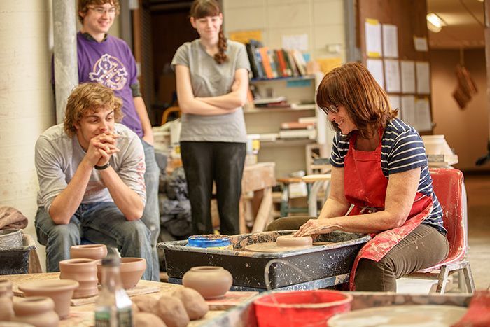 a teacher showing how to make pottery